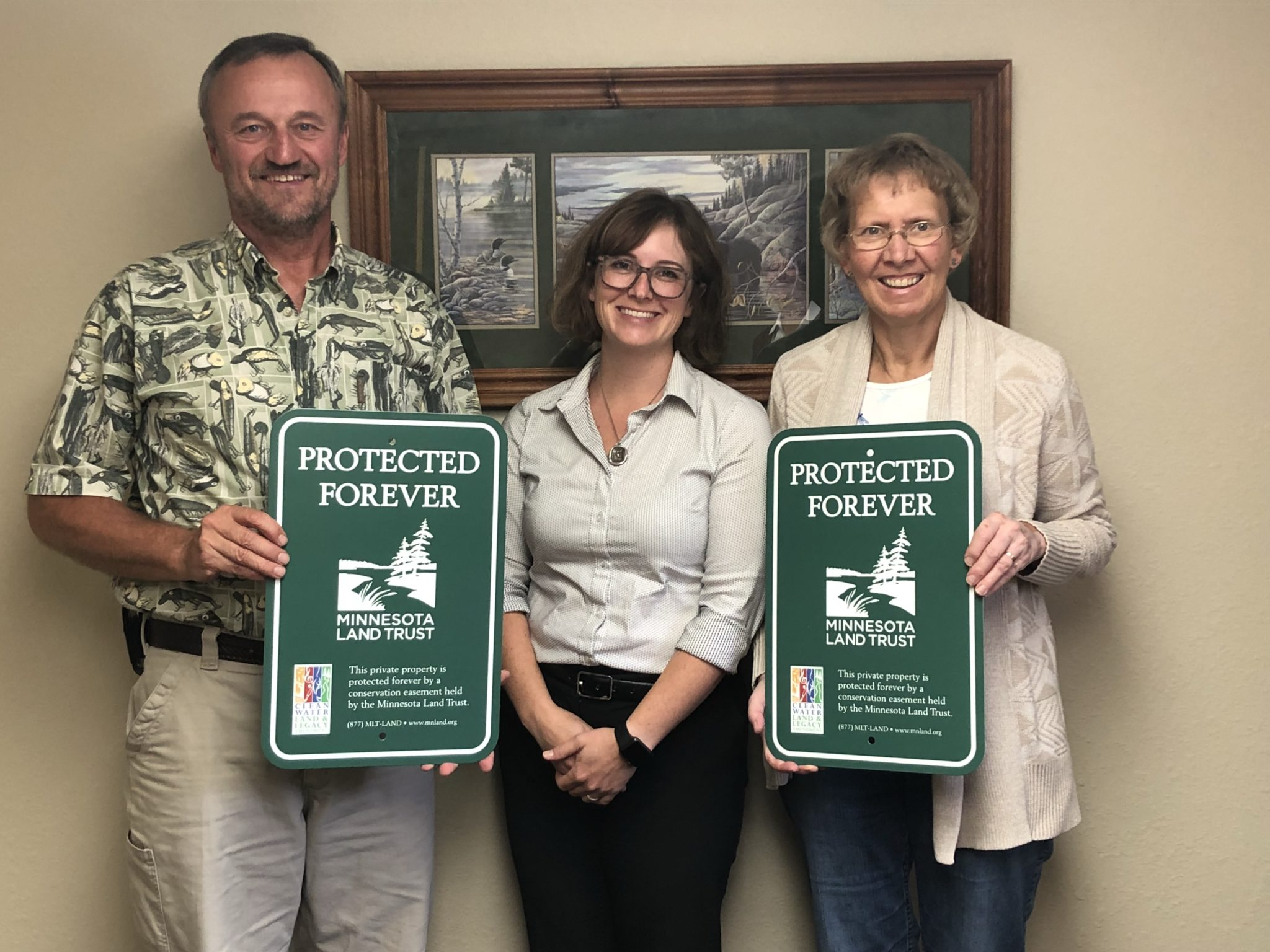 Gary Roerick, Vanessa Perry (Minnesota Land Trust), Sandy Roerick holding Protected Forever signs