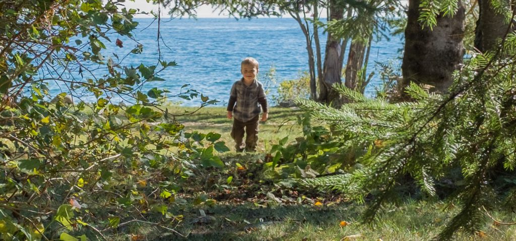 Boy walking in wooded area with Lake Superior in the background