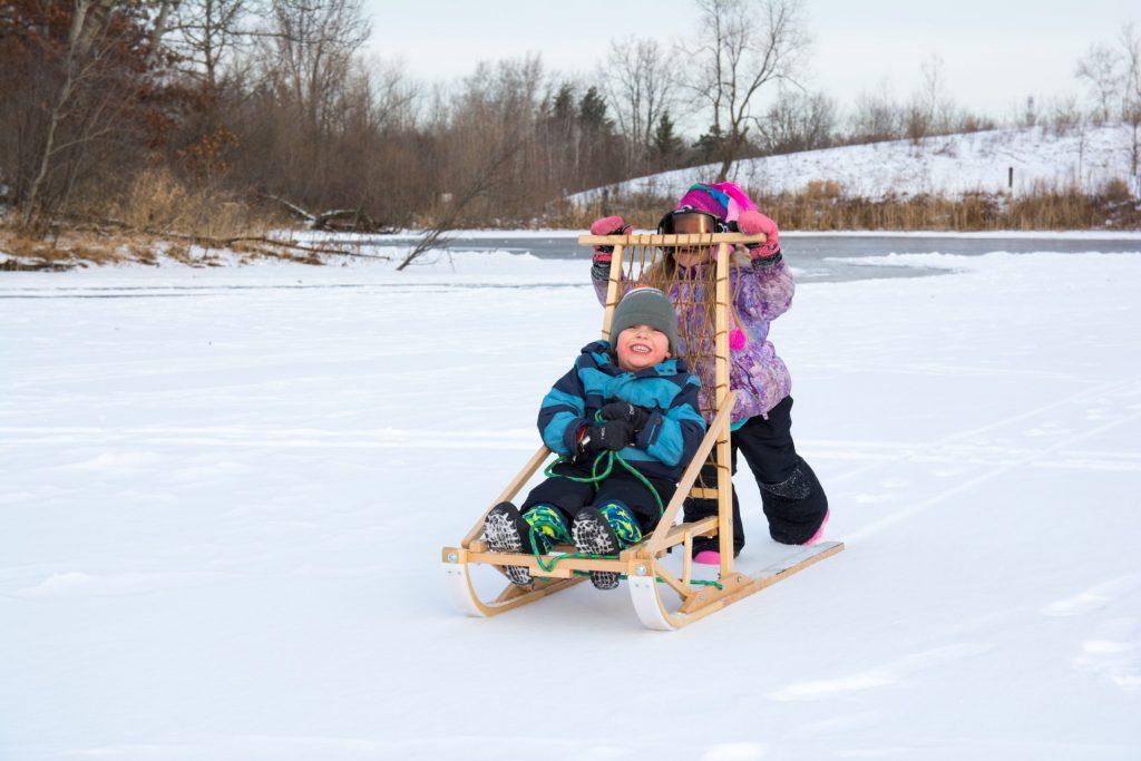 Kids kick sledding on a frozen lake