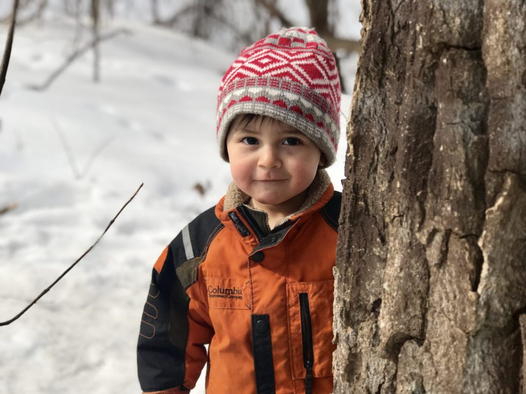 Young boy dressed in winter jacket standing next to a tree with snow in the background
